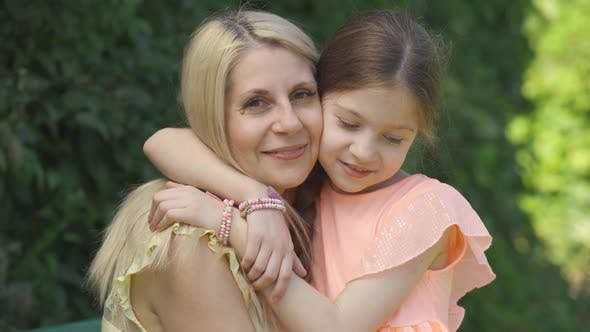 Thumbnail for Portrait of Blond Mother and Her Little Daughter Hugging in the Summer Park Looking at Camera