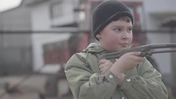 Thumbnail for Portrait of Cute Plump Red-cheeked Village Boy Playing with Toy Gun. Close-up of Little Charming