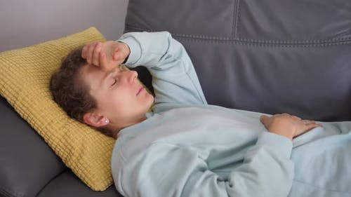 Young Woman on the Couch Touching Her Head Checking If She Has a High Temperature