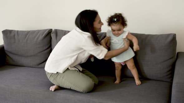 Happy Mother Sitting on Sofa with Her Cute Baby and Having Fun