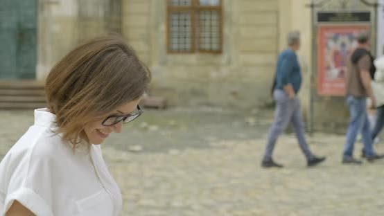 Cover Image for Mature Beautiful Woman Walking and Talking on Smartphone