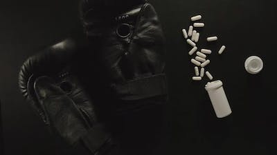 TOP VIEW: Boxing gloves falling next to pills and box of pills