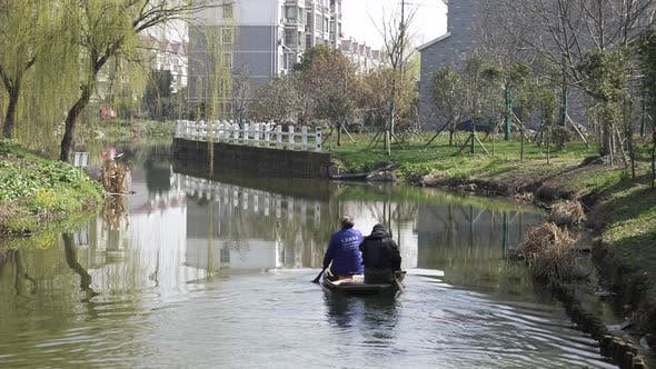 A Group Of Elderly Couples Rowing A Boat In A Small River V4