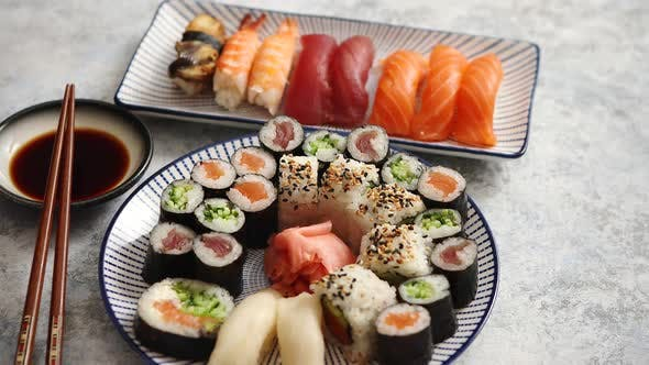 Thumbnail for Asian Food Assortment. Various Sushi Rolls Placed on Ceramic Plates