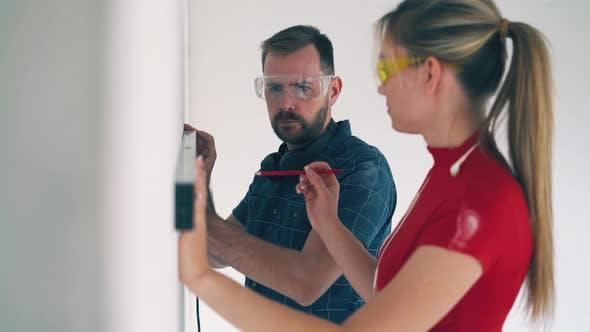 Joyful Couple Checks Wall Using Instrument in Spacious Room