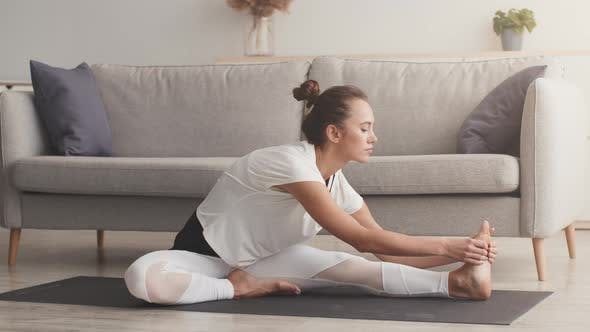 Young Sporty Woman Doing Yoga Stretching Exercises Practicing Pilates on Floor at Home