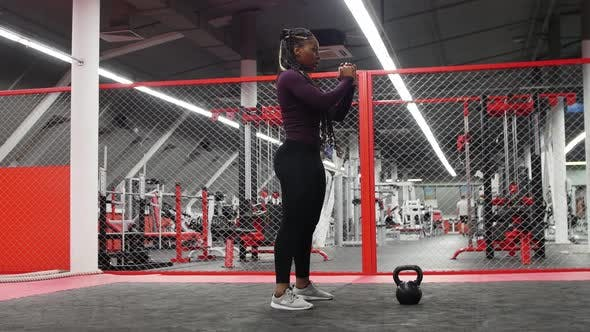 Sports in the Modern Gym  Africanamerican Woman Squatting