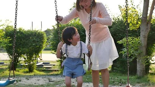 Asian Mother And Son Having Fun On Swing Together In The Park Slow Motion