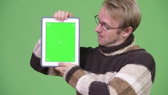 Thumbnail for Studio Shot of Happy Handsome Man Showing Digital Tablet