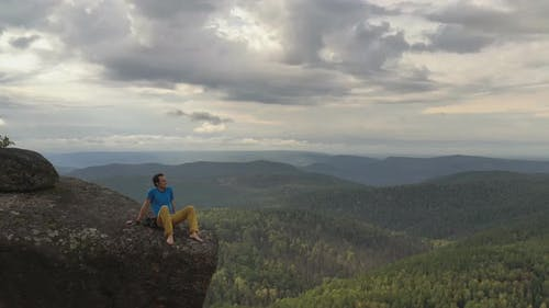 Aerial Shot of a Young Man Sitting on the Edge of a Cliff Enjoying the Solitude