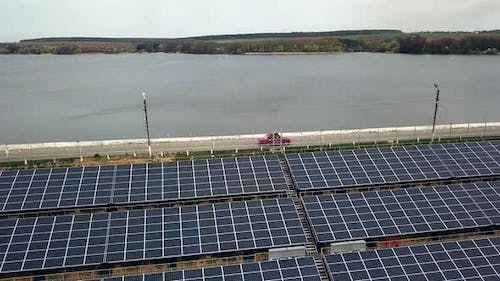 Solar panels near the river. Power station. Blue solar panels. Alternative source of electricity.