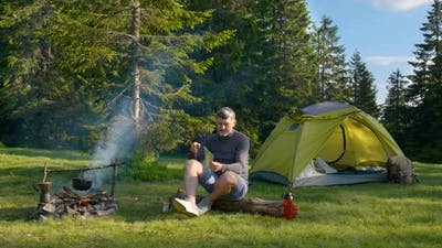 The Man Drinks Tea and Looks at the Map in the Camping