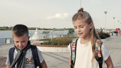 Boy and Girl with Backpacks Walking and Talking. Primary Education, Friendship, Childhood