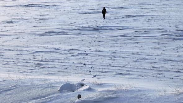 Thumbnail for Aerial View: Lonely Person Walks Through a Snowy Desert.