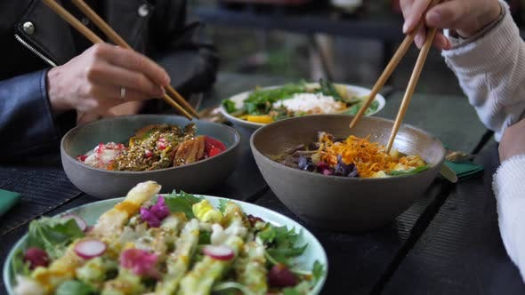 Thumbnail for Healthy Asian Vegan Lunch Served in Rustic Cafe. Two People Eating Their Healthy Vegan Meals with