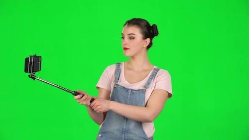 Girl Makes Selfie on Mobile Phone Using Selfie Stick on Green Screen