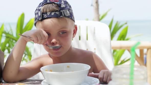 Kleiner Junge isst Haferbrei im Freien. Junge isst Haferbrei am Strand