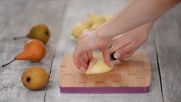 Thumbnail for Woman's Hands Cutting Pear on Wooden Cutting Board.