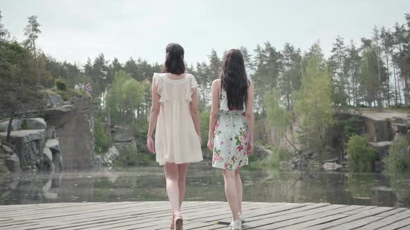 Cover Image for Two Cute Young Women Wear Summer Dresses Standing in the Top of Rock and Looking at Amazing View
