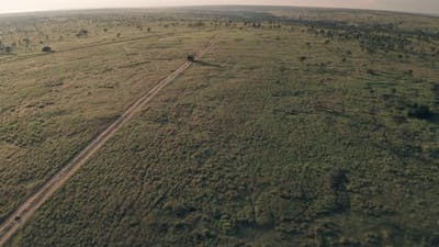 4 wheel drive vehicle on wildlife safari in Kenya. Aerial drone reveal of safari adventure