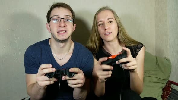 Thumbnail for Guy And Girl Are Playing On The Console Using Gamepads