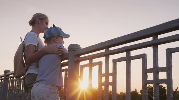 Cover Image for A Woman with Her Daughter Are Standing at the Railing of the Bridge at Sunset. Evening Walk with Mom