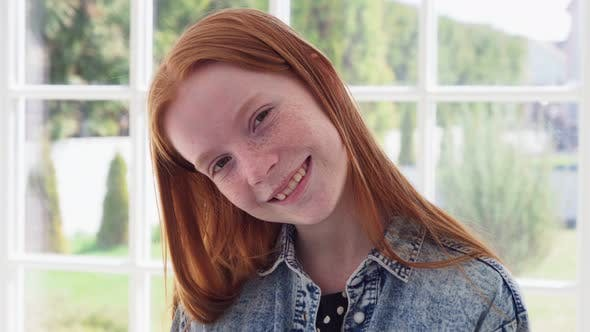 Funny Face of Teen Redhead Girl with Freckles Against White Window