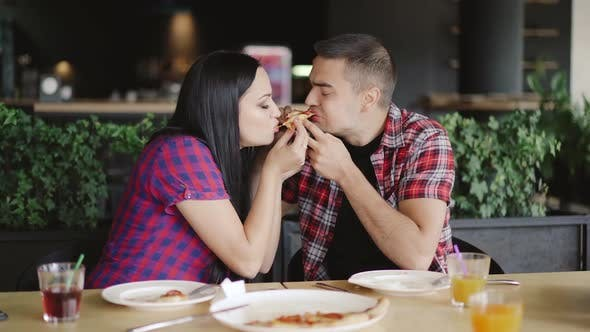 two people are eating one slice of pizza in the cafe. Loving couple is enjoying pizza together