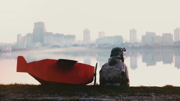 Thumbnail for Back View of Little Pilot Boy Sitting Near Amazing Peaceful City Lake