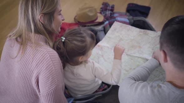 Thumbnail for Retour en haut Vue de la jeune famille caucasienne regardant la carte. Père amical, mère et fille faire