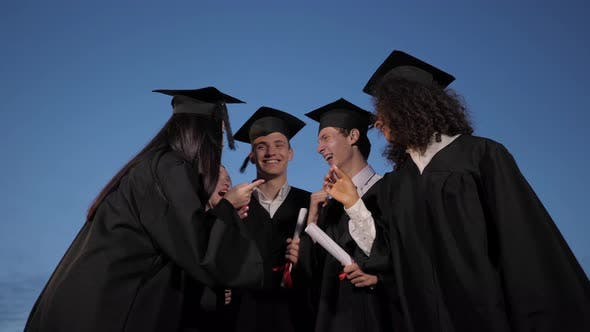 Thumbnail for Happy and Excited Group of Student Friends on Graduation Day Throw Their Caps Into the Air in the