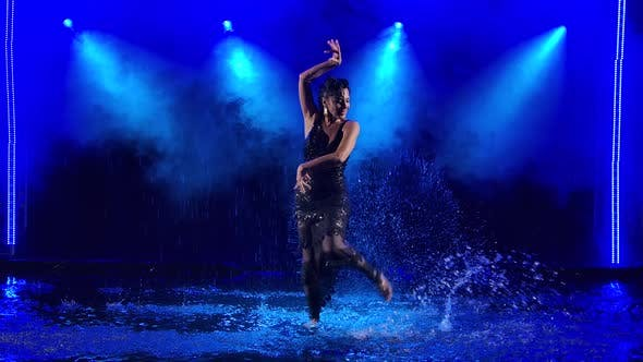 Thumbnail for Professional Dancer Dancing Flamenco in a Black Shiny Dress Against the Background of Falling Drops