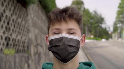Young student laughs in a medical protective mask near the road on an empty city street.
