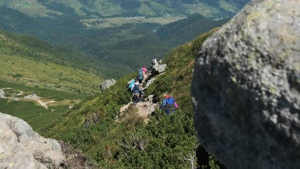 Thumbnail for Group of Tourists and Children with Backpacks Go Down on Stone Trail in Mountain