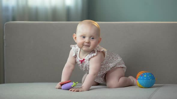 Healthy Baby Jumping on Sofa, Playing With Colorful Toys, Enjoying Happy Life