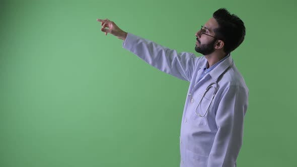 Thumbnail for Profile View of Happy Young Bearded Persian Man Doctor Pointing Finger