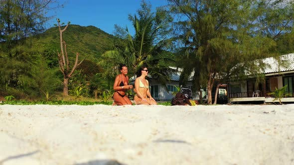 Thumbnail for Modern smiling girls travelling in the sun at the beach on clean white sand and blue background 4K