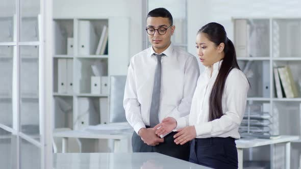 Thumbnail for Asian Woman and Arab Man Looking at AR device in Office