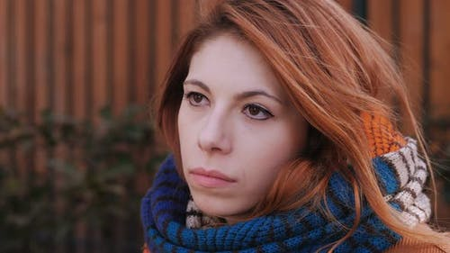 Sad pensive pretty young red hair woman thinking about her lost love-outdoor