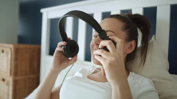 Thumbnail for Tracking Video der schwangeren Frau setzen Kopfhörer auf schwangeren Bauch