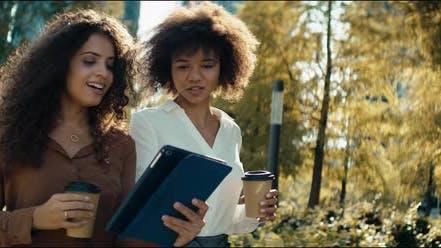 Video von lächelnden Geschäftsfrauen, die im Freien mit digitalem Tablet diskutieren.