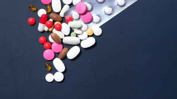 Colorful Pills Spilling on Dark Background Top Down