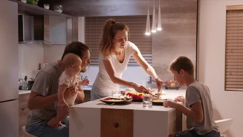 In the Kitchen Family of Four Having Supper Together