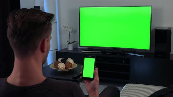 Thumbnail for A Man Watches a TV and Eventually Looks at a Smartphone in His Hand, TV and the Phone Green Screen