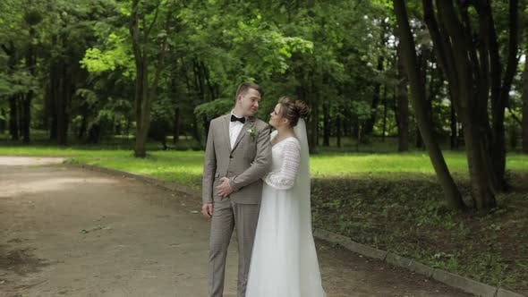 Thumbnail for Newlyweds. Caucasian Groom with Bride Walking, Embracing, Hugs in Park. Wedding Couple