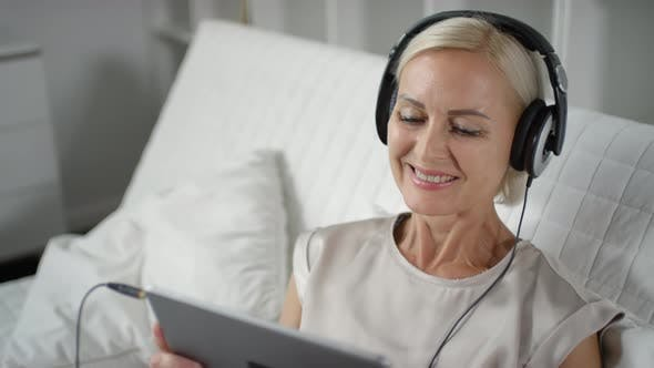 Thumbnail for Woman in Headphones Watching Video on Tablet and Smiling