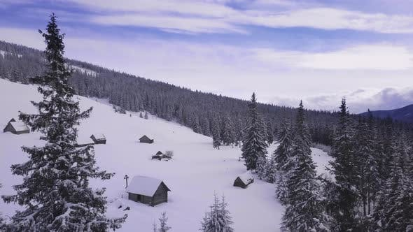 Thumbnail for Flying Over the Forest, Mountains and Shepherd Houses in Winter