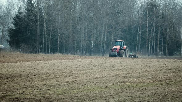 Farmer in a Tractor Cultivates the Soil with a Disc Harrow