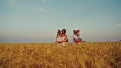 Loving Family Walking in Field in Summer
