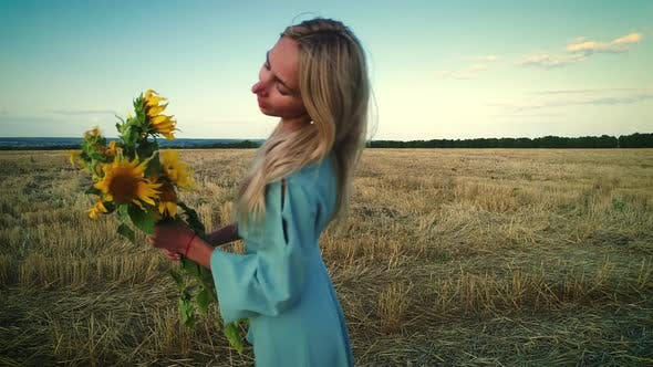 Thumbnail for Girl Sniffing Flowers. Young Sunflowers
